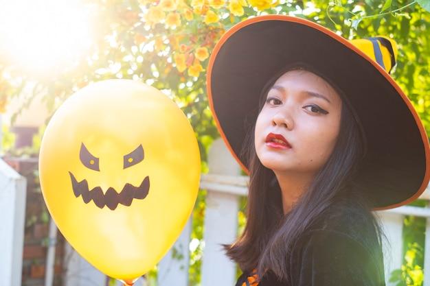 Halloween czarownica ze złym balonem na tle kwiatu.