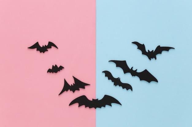 Halloween, dekoracje i straszna koncepcja. czarne nietoperze latają na różowym niebieskim