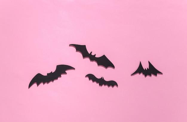 Halloween, dekoracje i straszna koncepcja. czarne nietoperze latają nad różowym jasnym
