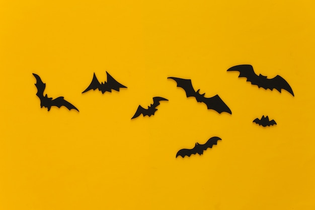 Halloween, dekoracje i straszna koncepcja. czarne nietoperze latają nad żółtym