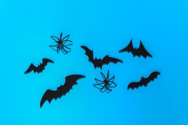 Halloween, dekoracje i straszna koncepcja. pająki i czarne nietoperze latają nad błękitnym jasnym