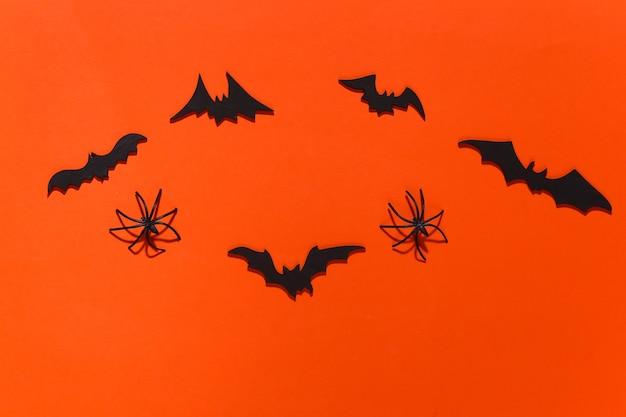 Halloween, dekoracje i straszna koncepcja. pająki i czarne nietoperze latają nad jaskrawą pomarańczą