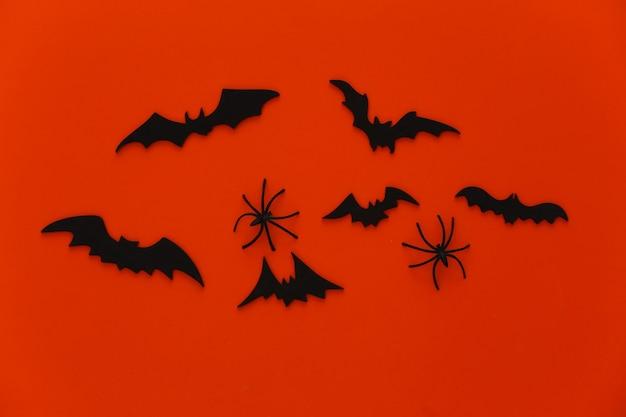 Halloween, dekoracje i straszna koncepcja. pająki i czarne nietoperze latają nad pomarańczą