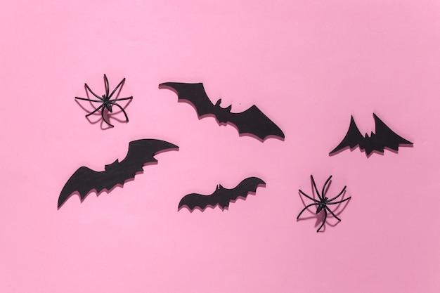 Halloween, dekoracje i straszna koncepcja. pająki i czarne nietoperze latają nad różowym jasnym