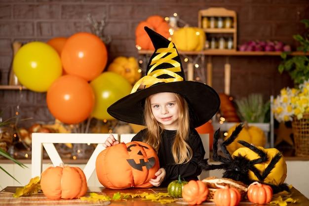 Halloween, dziecko dziewczynka w stroju wiedźmy z dyniami i dużym pająkiem w ciemnej kuchni dekoruje dynię podczas obchodów halloween