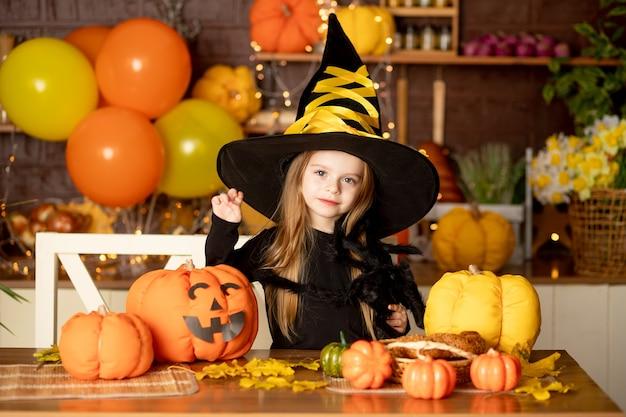 Halloween, dziecko dziewczynka w stroju wiedźmy z dyniami i dużym pająkiem w ciemnej kuchni przeraża podczas obchodów halloween