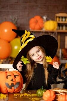 Halloween, dziecko dziewczynka w stroju wiedźmy z dyniami i dużym pająkiem w ciemnej kuchni straszy lub bawi się liśćmi podczas obchodów halloween