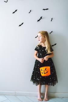 Halloween dziecko portret blondynka ubrana w czarną sukienkę z wiaderkiem z dyni cukierków i nietoperze na ścianie za nią. cukierek albo psikus na wakacje. skopiuj miejsce.