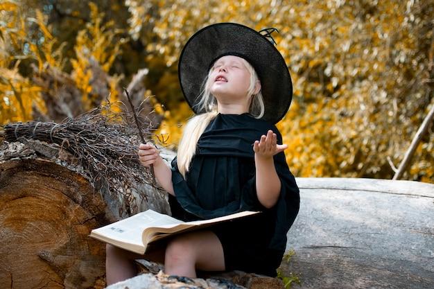 Halloween i czarownice. dziecko w stroju wiedźmy. dziecko siedzi na drzewie z książką i czarodziejską różdżką. jesień, las