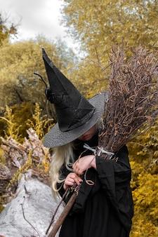 Halloween i czarownice. dziewczyna w czarnym kapeluszu z miotłą w rękach w jesiennym lesie