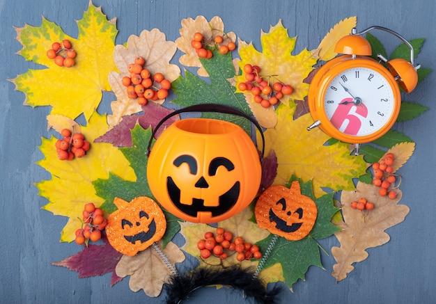 Halloween jack o lantern z cukierkami na kolorowym jesiennym tle suszonych liści, pomarańczowych jagód jarzębiny i budzika. kartka świąteczna halloween. koncepcja czasu wakacji na halloween