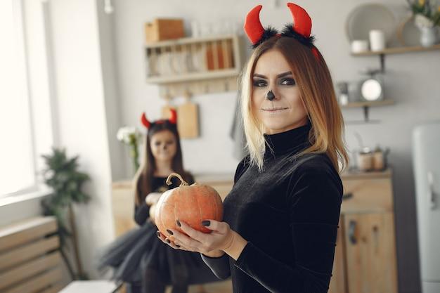Halloween. matka i córka w kostiumie na halloween. rodzina w domu.