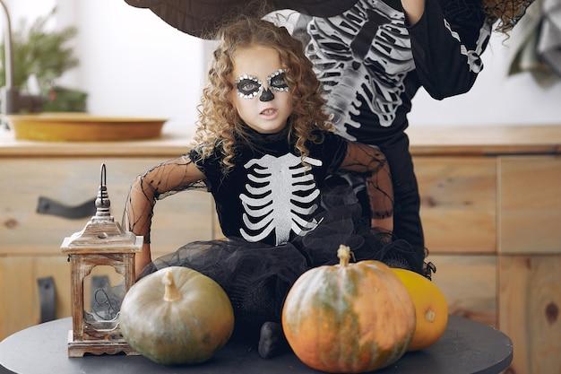 Halloween. matka i córka w meksykańskim stroju na halloween. rodzina w domu z baniami.