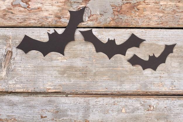 Halloween papierowe nietoperze czarne papierowe nietoperze latające nad drewnianym tłem koncepcja dekoracji halloween