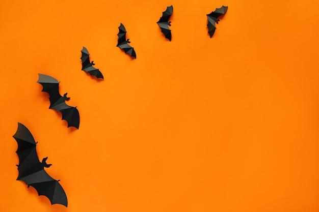 Halloween. papierowe nietoperze na pomarańczowym tle, płaski układ, kartka z życzeniami