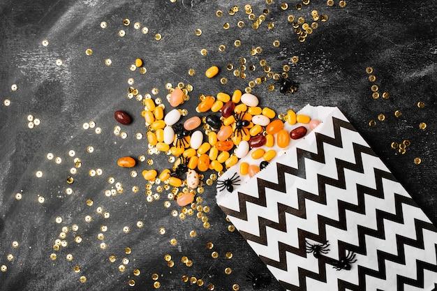Halloween party trick of treat candy z cukierkami płynącymi z torby na przyjęcie na ciemnym tle drewna płaska świecka, widok z góry modna koncepcja wakacje.