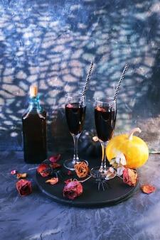 Halloween pije wino dynie mistyczne dekoracje suche róże i cienie na czarnym tle