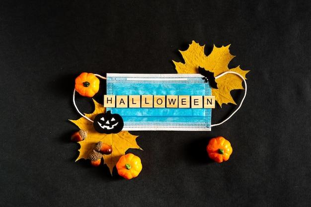 Halloween podczas pandemii z żółtymi liśćmi i maską medyczną