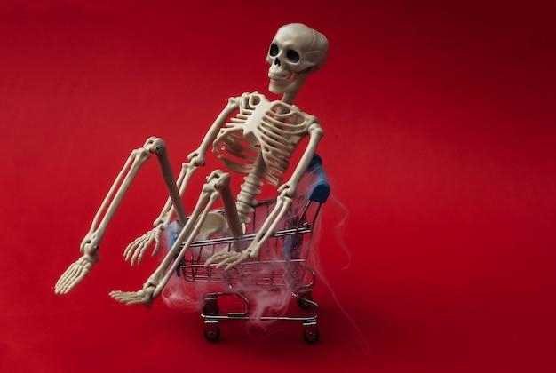 Halloween, przerażający motyw. fałszywy szkielet i wózek na zakupy w sieci na czerwono.