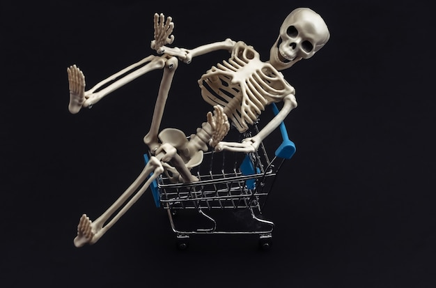 Halloween, przerażający motyw. szkielet i wózek na zakupy na czarno.