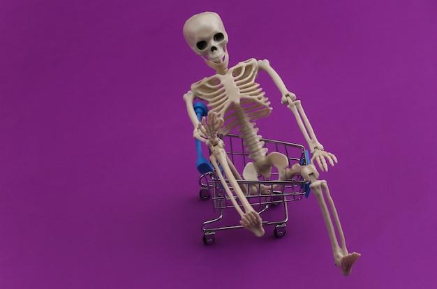 Halloween, przerażający motyw. szkielet i wózek na zakupy na fioletowo.
