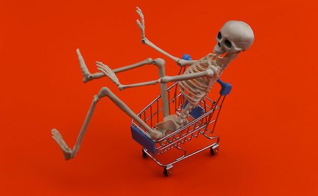 Halloween, przerażający motyw. szkielet i wózek na zakupy na pomarańczowo.