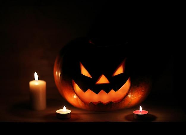 Halloween rzeźbiona bania i świeca na tle