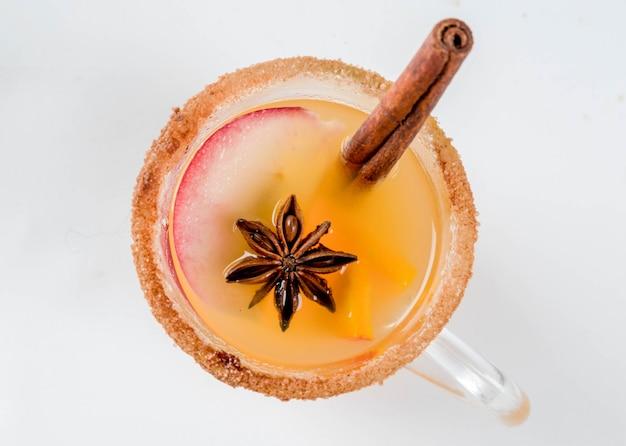Halloween święto dziękczynienia tradycyjne jesienne zimowe napoje i koktajle pikantna gorąca sangria dyniowa z anyżem jabłkowo-cynamonowym na białym marmurowym stole w szklanych kubkach