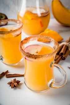 Halloween, święto dziękczynienia. tradycyjne jesienne, zimowe napoje i koktajle. pikantna gorąca sangria dyniowa z jabłkiem, cynamonem i anyżem. na białym marmurowym stole, w szklanych kubkach. selektywne ustawianie ostrości, bliski widok