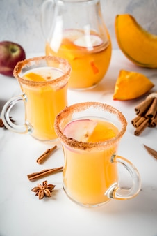 Halloween, święto dziękczynienia. tradycyjne jesienne, zimowe napoje i koktajle. pikantna gorąca sangria dyniowa z jabłkiem, cynamonem i anyżem. na białym marmurowym stole, w szklanych kubkach. selektywne ustawianie ostrości, kopiowanie miejsca