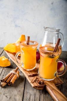 Halloween, święto dziękczynienia. tradycyjne jesienne, zimowe napoje i koktajle. pikantna gorąca sangria dyniowa z jabłkiem, cynamonem i anyżem. na starym rustykalnym drewnianym stole, w szklanych kubkach. przestrzeń kopiowania selektywnej ostrości