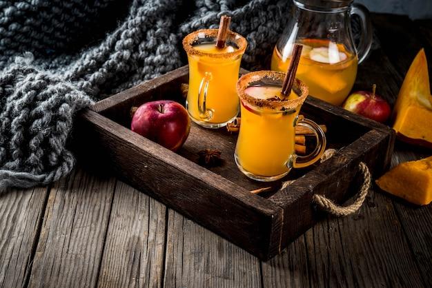 Halloween, święto dziękczynienia. tradycyjne jesienne, zimowe napoje i koktajle. pikantna gorąca sangria dyniowa z jabłkiem, cynamonem i anyżem. w zasobniku rustykalny drewniany stół, szklane kubki. przestrzeń kopiowania selektywnej ostrości