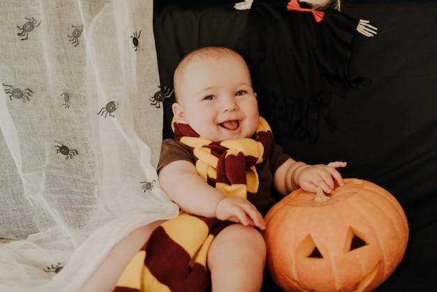 Halloween, szczęśliwy mały chłopiec uśmiecha się i śmieje z dyni jacka