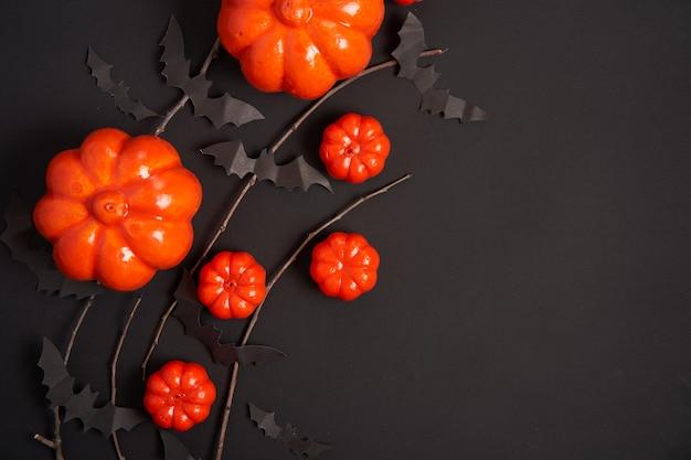 Halloween tło, pomarańczowe ozdobne plastikowe dyni czarny papier nietoperz sucha gałąź tektura