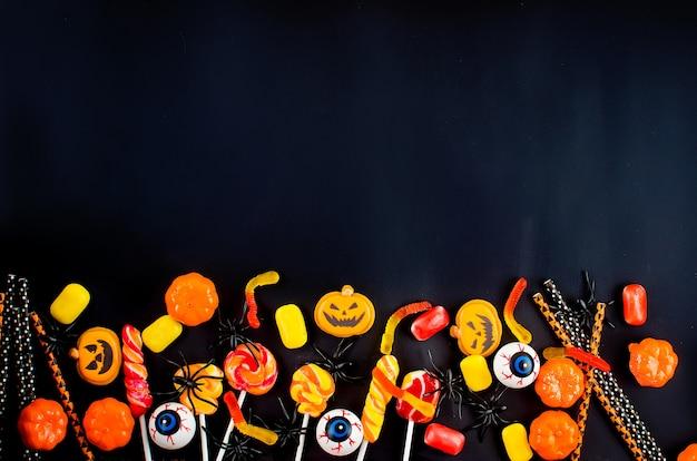 Halloween tło z wieloma oczami dyni, cukierków i pająków