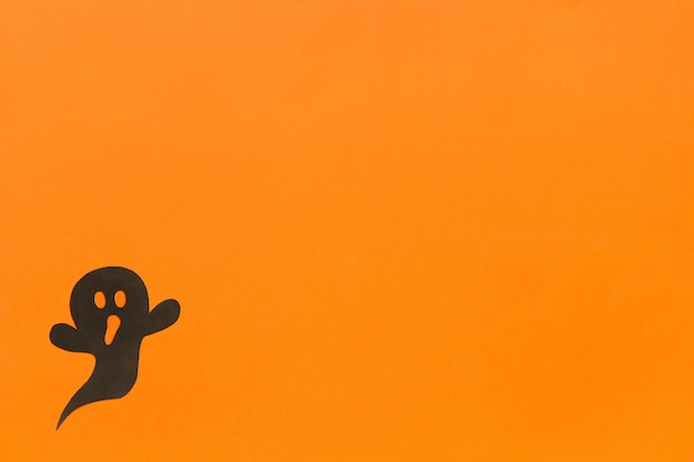 Halloween w tle. czarny papier duch na pomarańczowym tle
