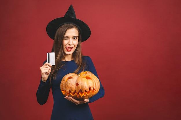 Halloween witch z rzeźbioną dynią i kartą kredytową - na białym tle na czerwonym tle. emocjonalna młoda kobieta w kostiumie na halloween.