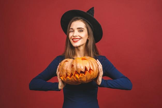 Halloween witch z rzeźbioną dynią - na białym tle na czerwonym tle. emocjonalna młoda kobieta w kostiumie na halloween.