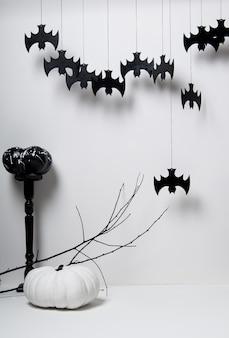 Halloween z czarnymi sylwetkami nietoperzy i dyni z gałęzią drzewa na białym tle