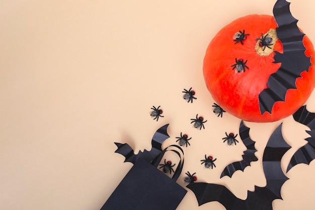 Halloween z dyniami, pająkami, pajęczynami i nietoperzem na beżowym tle. koncepcja przyjęcia na halloween