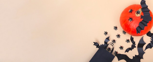 Halloween z dyniami, pająkami, pajęczynami i nietoperzem na beżowym tle. koncepcja strony halloween. transparent