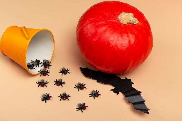 Halloween z dyniami, pająkami, żółtym wiaderkiem, muchami i nietoperzem na beżowym tle. koncepcja przyjęcia na halloween