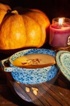 Halloween ze świeczkami z zupą dyniową i kremową na strasznej nocy - scena halloween.