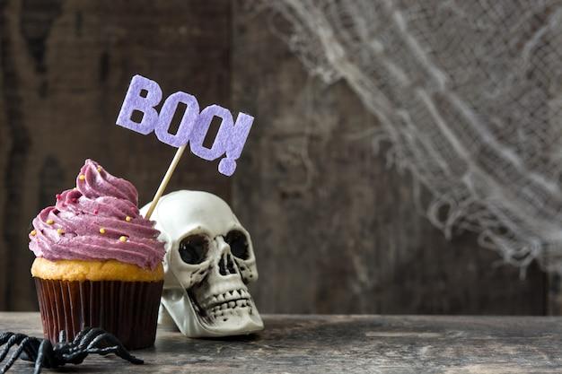 Halloweenowa babeczka i czaszka na drewnianym stole