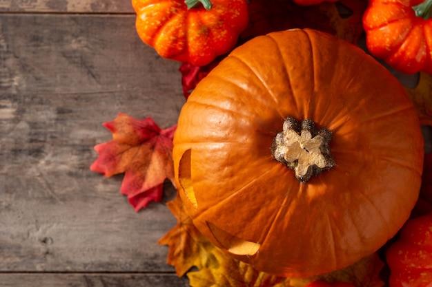 Halloweenowa bania i jesienne liście na drewnianym stole