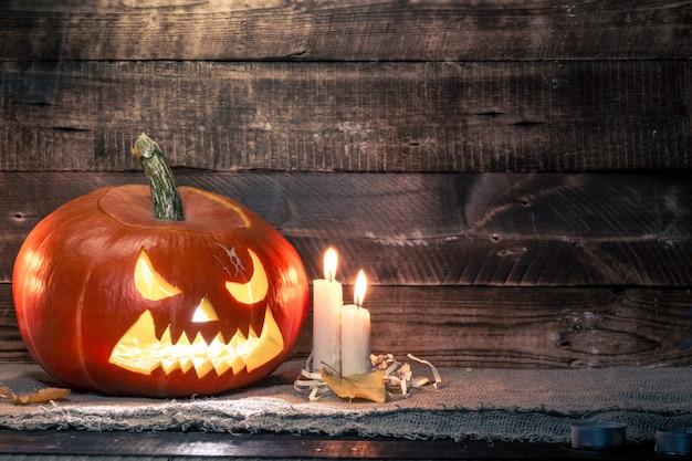 Halloweenowa bania i świeczki na ciemnym, drewnianym tle. świętowanie halloween. skopiuj miejsce halloween