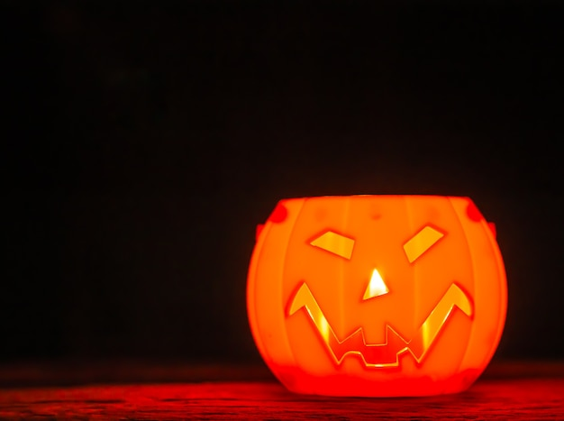 Halloweenowa bania na czarnym tle, straszny uśmiech.