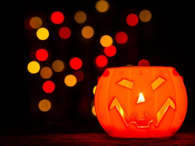Halloweenowa bania z bokeh tłem, straszny uśmiech.