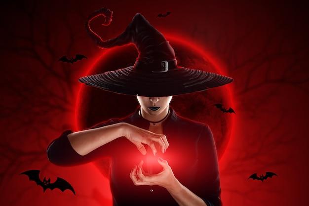 Halloweenowa czarownica wyczarowuje na tle księżyca. piękna młoda kobieta w kapeluszu czarownicy.