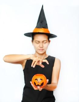 Halloweenowa czarownica z magiczną banią na białym tle.